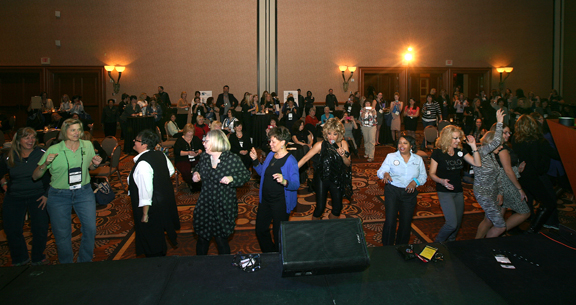 Women at the conference dancing on a dance floor at the networking reception.