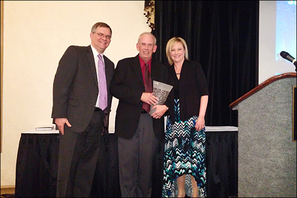 David Bywater, MAS, CEO of Bankers Advertising (left) and Erica Kelley-Gogel, CAS, the distributor's vice, present Tim Chamberlain with the Sales Person of the Year.