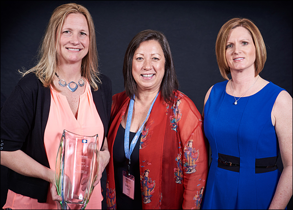 (From left) Christina Hamilton, account executive at SanMar and Susan Rye, director of strategic accounts at SanMar, receive the supplier's Supplier of the Year trophy with Vicki Palm, director of marketing at The Vernon Company.