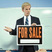 A man holding a for sale sign