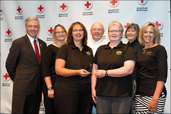 Site Bloodmobile Committee Chairperson Donna Dewanz (center left) accepts the American Red North Central Blood Services Region's Outstanding Blood Drive Sponsor Award from Phil Hansen, regional CEO, American Red Cross Minnesota Region (left) and Kerry Cipra, account manager, American Red Cross North Central Blood Services (center right). Dewanz is joined on stage by (from second left) Tami Murphy, Sleepy Eye Site Manager Warren Harris and Betty Jensen.