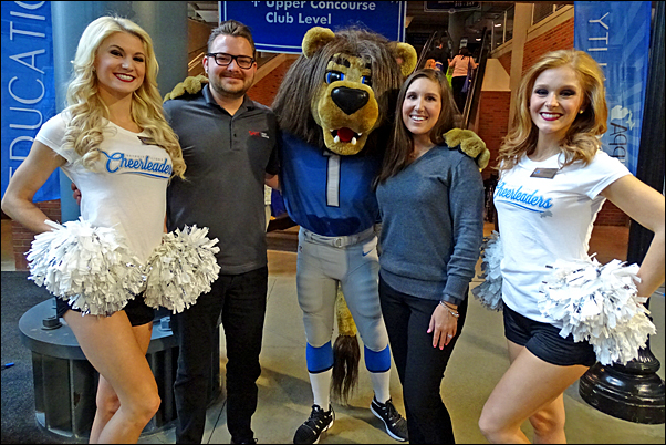 tefanie Poe and Cody Miller from SAGE get a photo with Detroit Lions' cheerleaders and the team's mascot, ROARY.