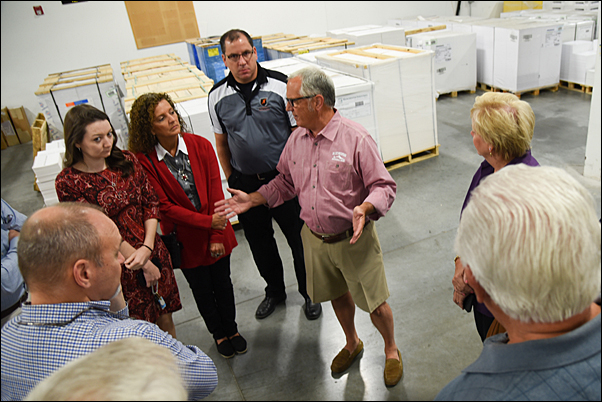 Tom Metz, CEO and president of TradeNet (center), leads a tour of the supplier's factory.