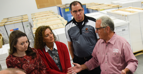 Tom Mertz, CEO and president of TradeNet (right), leads a tour of the supplier's factory.
