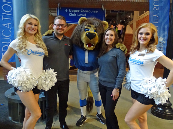 Cody Miller and Stefanie Poe from SAGE get a photo with Detroit Lions' cheerleaders and the team's mascot, ROARY.