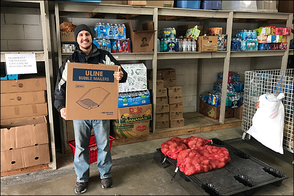Halls & Company's Zach Zinder helps unload the supplier's food donation to North-Suburban Emergency Assistance Response.