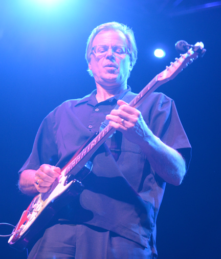 Joe Scott playing guitar on stage with his band.