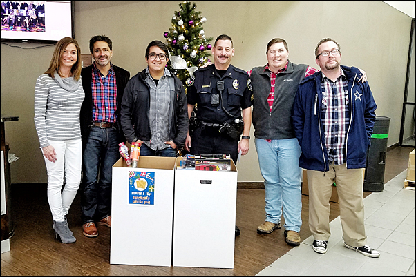 Sgt. Brian Morales (center) of the Irving Police Department visited PPAI headquarters on Friday to collect the more than $1,600 in toys and funds staff had donated to the Irving Police and Fire Blue Christmas Organization and meet with Association staff.