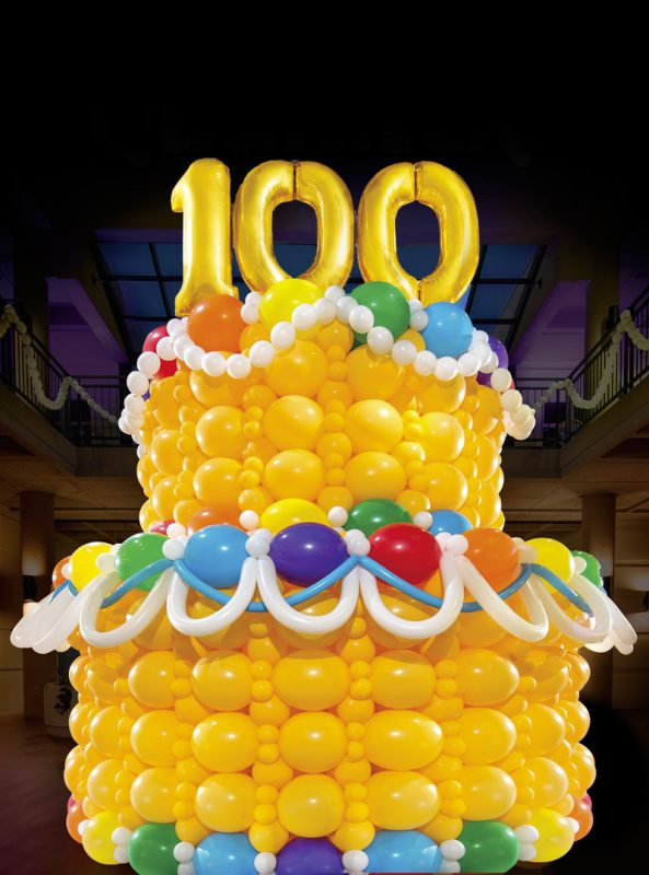 This is a large cake made out of balloons with the number 100 made out of balloons at the top.